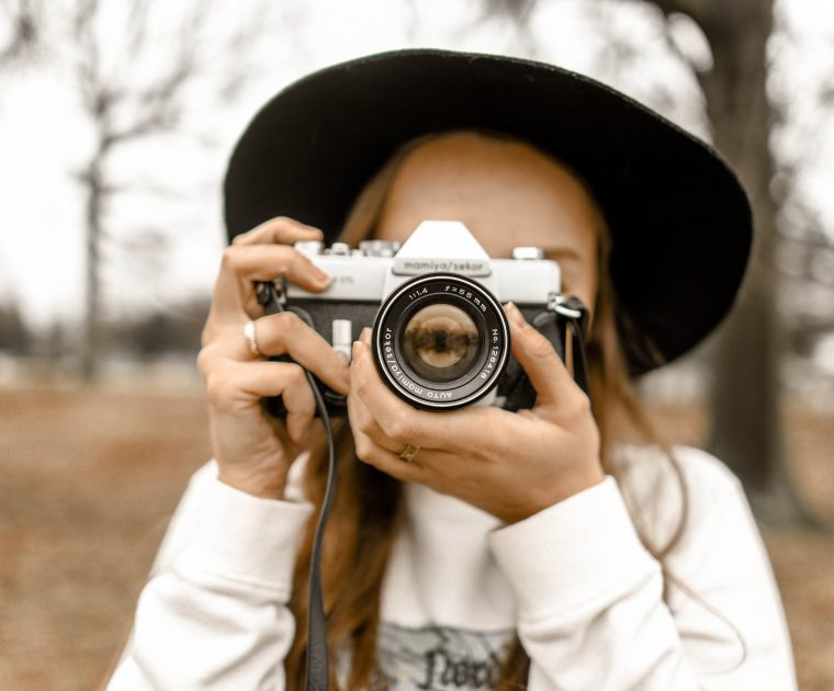 woman using a camera with trees behind